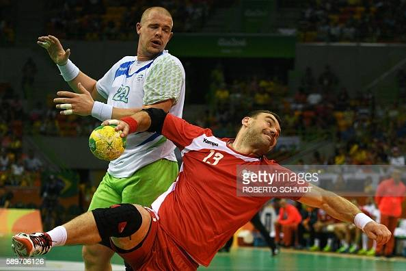 Poland's pivot Bartosz Jurecki shoots past Slovenia's pivot Matej Gaberduring the men's preliminaries Group B handball match Poland vs Slovenia for...