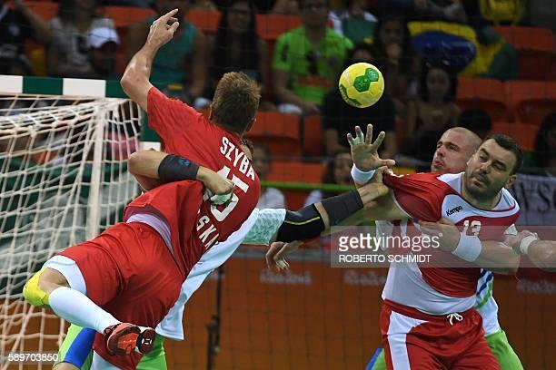 Poland's pivot Bartosz Jurecki vies with a Slovenian player during the men's preliminaries Group B handball match Poland vs Slovenia for the Rio 2016...