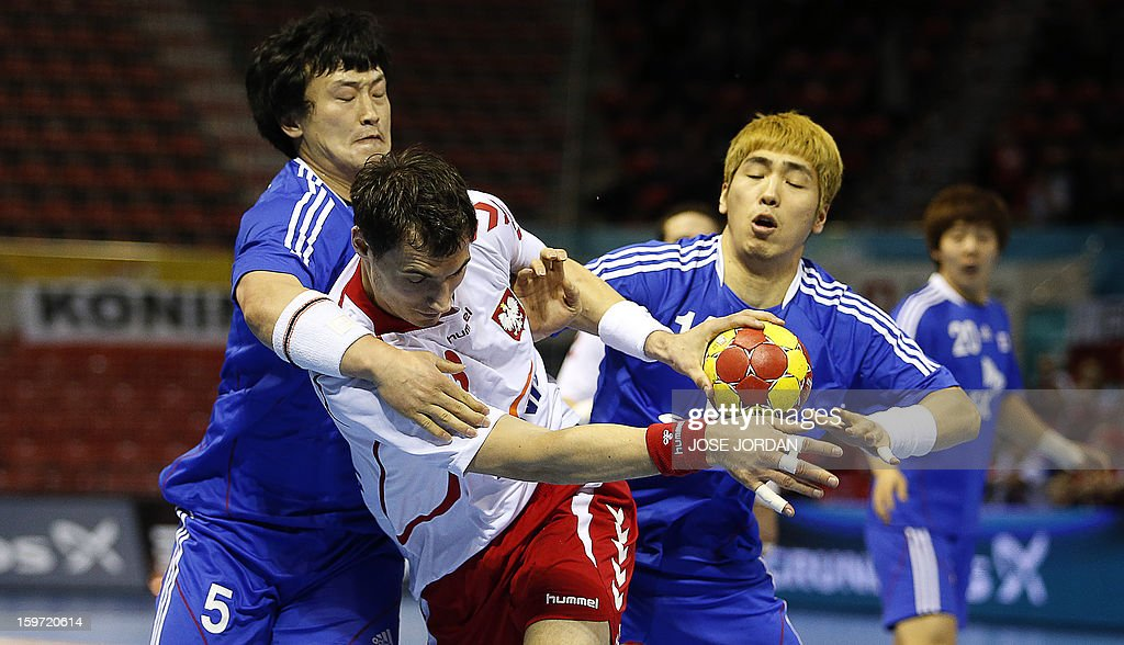 Poland's right back Krzystof Lijewski (C) vies with Korea's pivot Park Kyung-Suk (L) and Korea's back Yoon Ci-Yoel during the 23rd Men's Handball World Championships preliminary round Group C match Poland vs South Korea at the Pabellon Principe Felipe in Zaragoza on January 19, 2013. AFP PHOTO/ JOSE JORDAN