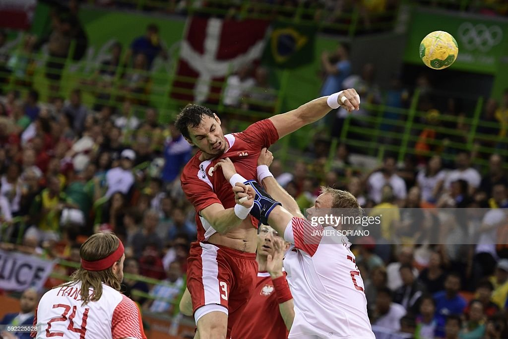 Poland's right back Krzysztof Lijewski shoots past Denmark's pivot Rene Toft Hansen during the men's semifinal handball match Poland vs Denmark for...