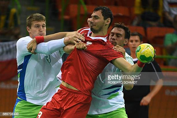 Poland's right back Krzysztof Lijewski vies with Slovenia's pivot Blaz Blagotinsek during the men's preliminaries Group B handball match Poland vs...