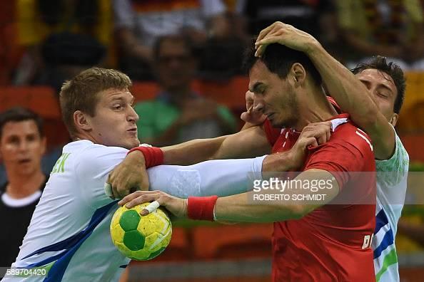 TOPSHOT Poland's right back Krzysztof Lijewski vies with Slovenia's pivot Blaz Blagotinsek during the men's preliminaries Group B handball match...