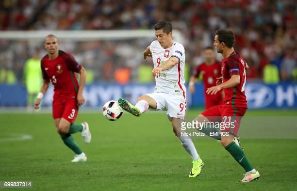 Poland's Robert Lewandowski and Poland's Bartosz Kapustka battle for the ball