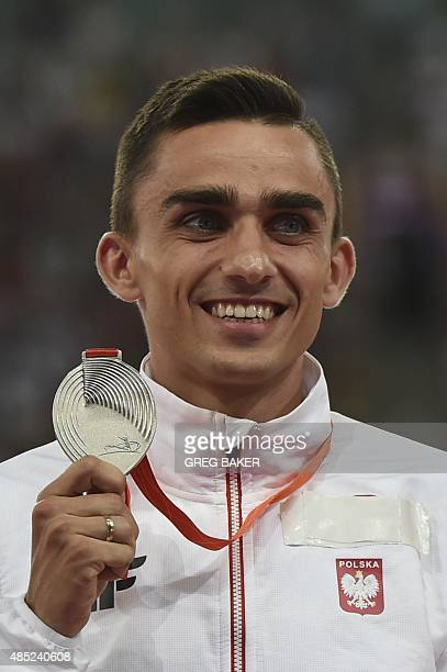 Poland's silver medallist Adam Kszczot bites his medal on the podium during the victory ceremony for the men's 800 metres athletics event at the 2015...