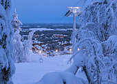 Beautiful evening panorama landscape view on Levi ski resort in Laplandia, Finland, with ski lift, village and trees covered by snow. Seasonal winter greeting card background.