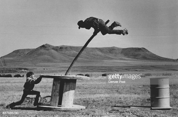 3/1/1986 MAR 7 1986 'Pole bull' an old cable wheel and a corral post make a practice bull ride for Tony Mitchell with the help of playmate Shannon...