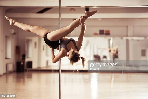 Pole dancer exercising ceiling splits in a dance studio.