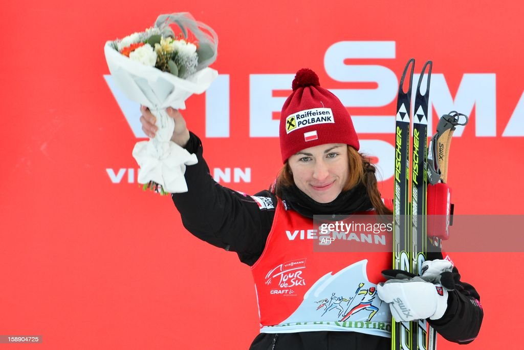 Pole Justyna Kowalczyk celebrates on the podium of the women's Tour de Ski , Stage four 15km free pursuit in Toblach on January 3, 2013. Poland's Justyna Kowalczyk won ahead of Charlotte Kalla of Sweden and Therese Johaug of Norway . AFP PHOTO / GIUSEPPE CACACE