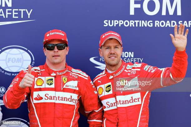 Pole position qualifier Kimi Raikkonen of Finland and Ferrari celebrates with Sebastian Vettel of Germany and Ferrari in parc ferme during qualifying...