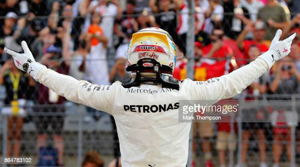 Pole position qualifier Lewis Hamilton of Great Britain and Mercedes GP waves to the crowd from parc ferme during qualifying for the United States...