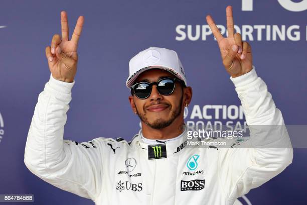 Pole position qualifier Lewis Hamilton of Great Britain and Mercedes GP celebrates in parc ferme during qualifying for the United States Formula One...