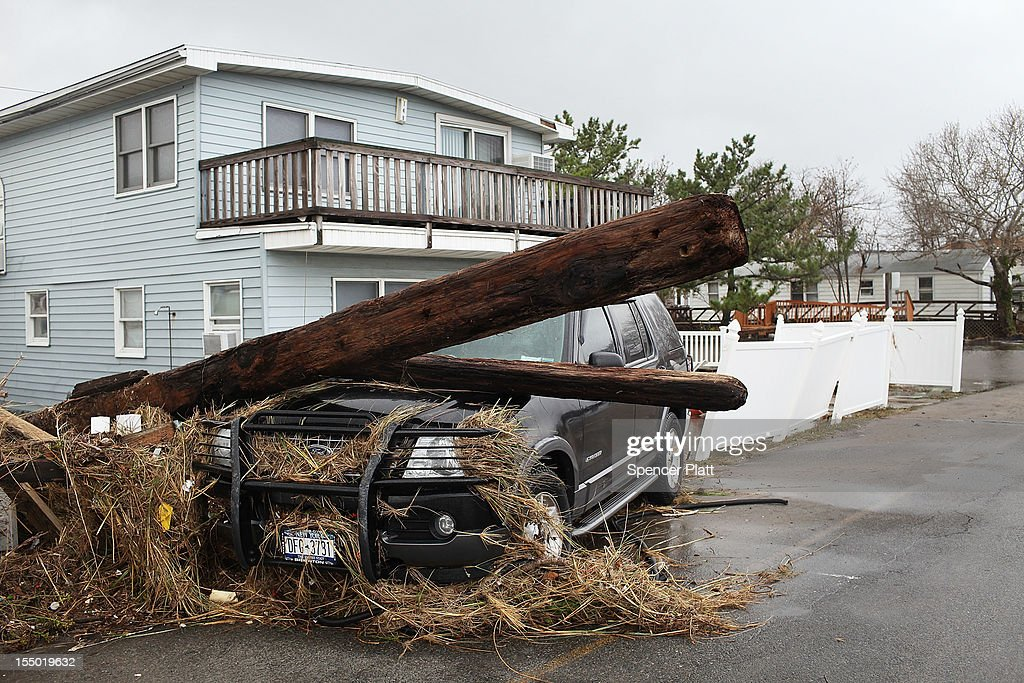 A pole sits on the hood of a SUV on October 30, 2012 in the Breezy Point Neighborhood of the Queens borough of New York City. At least 40 people were reportedly killed in the U.S. by Sandy as millions of people in the eastern United States have awoken to widespread power outages, flooded homes and downed trees. New York City was hit especially hard with wide spread power outages and significant flooding in parts of the city.