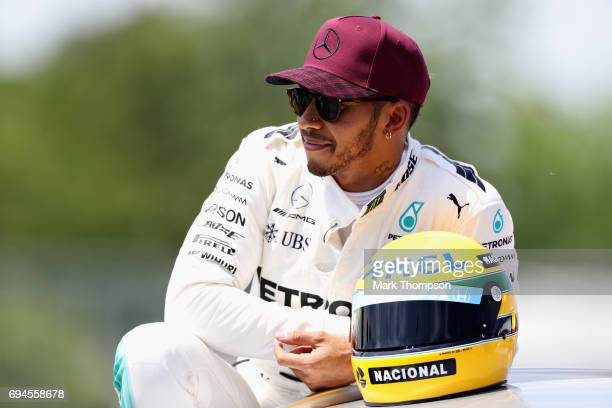 Pole sitter Lewis Hamilton of Great Britain and Mercedes GP with a commemorative helmet of F1 legend Ayrton Senna after he beat the previous record...