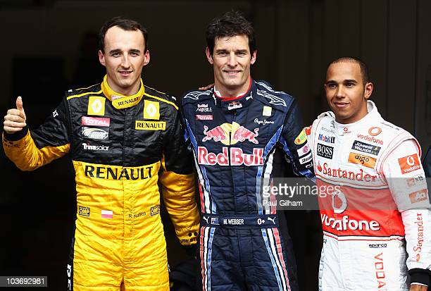 Pole sitter Mark Webber of Australia and Red Bull Racing celebrates in parc ferme with second placed Lewis Hamilton of Great Britain and McLaren...