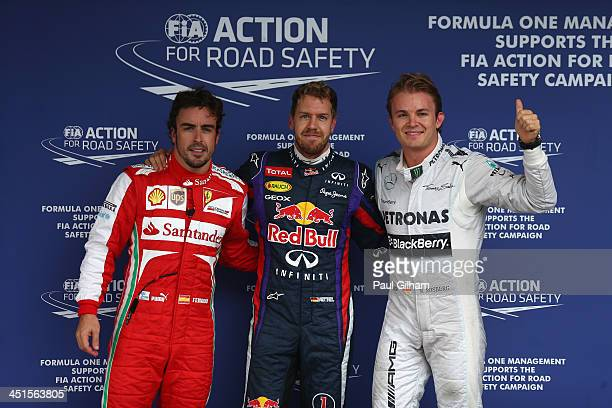 Pole sitter Sebastian Vettel of Germany and Infiniti Red Bull Racing celebrates with second placed Nico Rosberg of Germany and Mercedes GP and third...