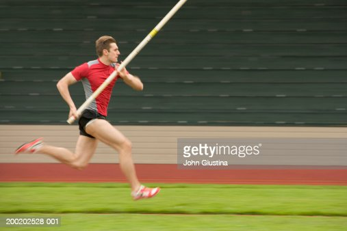 Pole vaulter running with pole, side view (blurred motion)