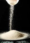 Polenta flour being poured into a bowl.