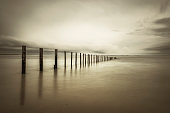 Beach poles in the sea on a tranquil cloudy day. Sepia toned image.