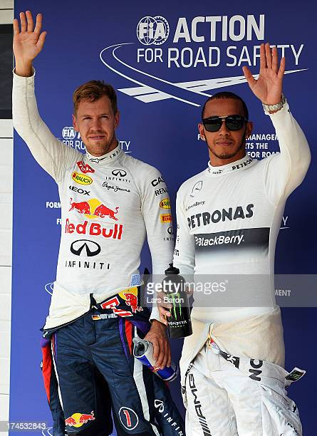 Polesitter Lewis Hamilton of Great Britain and Mercedes GP celebrates with second placed Sebastian Vettel of Germany and Infiniti Red Bull Racing...