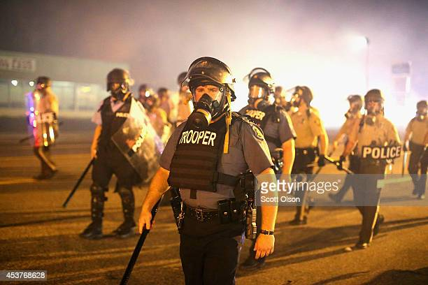 Police advance through a cloud of tear gas toward demonstrators protesting the killing of teenager Michael Brown on August 17 2014 in Ferguson...