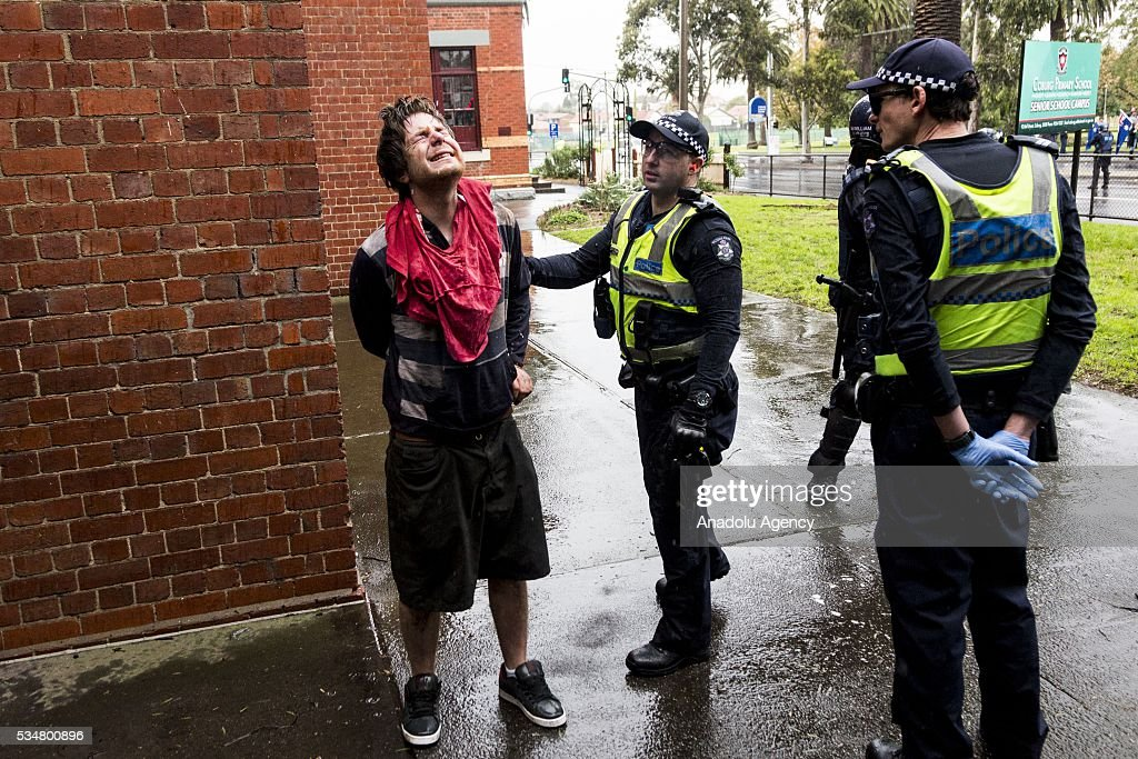 Police advices a handcuffed True Blue Crew protestor to look up to get rain water to clean his face after he was pepper sprayed during a 'Say No To Racism' protest and a counter 'Stop the Far Left' rally in Coburg Melbourne, Australia on May 28, 2016. Seven men were arrested after a violent brawl erupted between rival protesters at an anti-racism rally in Melbourne's inner-north. Anti-Facists clashed with Anti-Islam nationalists who go by the name 'True Blue Crew'.