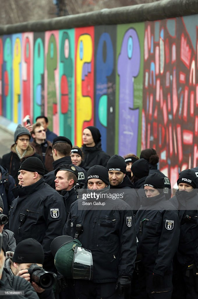 Police, after scuffles with protesters, stand guard at the East Side Gallery, which is the longest still-standing portion of the former Berlin Wall, following efforts by a construction company to remove a 25-meter long section of the Wall on March 1, 2013 in Berlin, Germany. A real estate developer is planning to build a 14-storey apartment building between the East Side Gallery and the Spree River, and needs to remove the Wall section in order to allow access to the construction site. Critics, including East Side Gallery mural artists and Spree River embankment development opponents, decry the move, citing the importance of the East Side Gallery's status as a protected landmark and a major tourist attraction. The East Side Gallery is approximately 1.3 kilometers long.