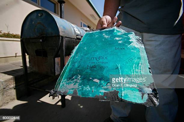 A police agent from the Bolivian specialized conternarcotics force holds a sheet of glass fiber coated with carbon which was used to conceal two...