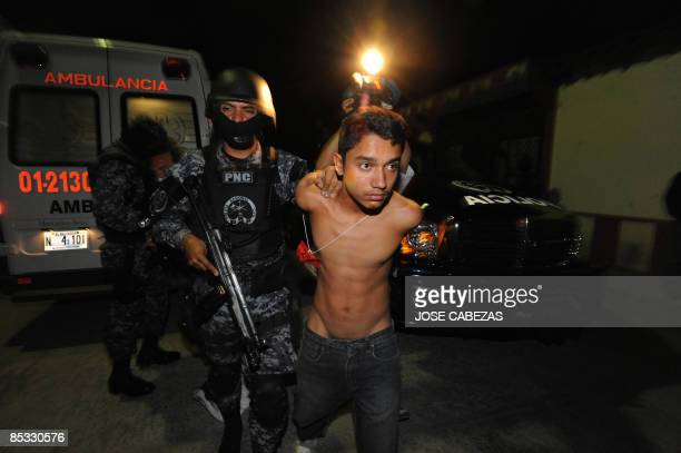 Police agents secure an alleged member of the Mara Salvatrucha gang during an anti gang operation in the early hours of March 10 2009 in the town of...