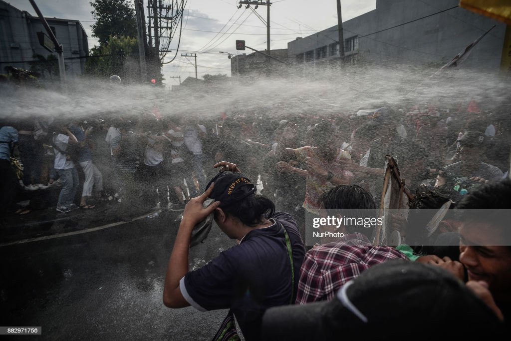 """Police aim a water cannon at protesters during a demonstration against President Rodrigo Duterte in Manila, Philippines, November 30, 2017. Thousands of President Duterte's critics staged protests to condemn his plan of setting up a """"revolutionary government"""", fearing it may lead to a dictatorship. The protests come after President Duterte ordered government troops to eliminate communist rebels and left-wing groups, labelling them as terrorists. Ezra Acayan/NurPhoto"""