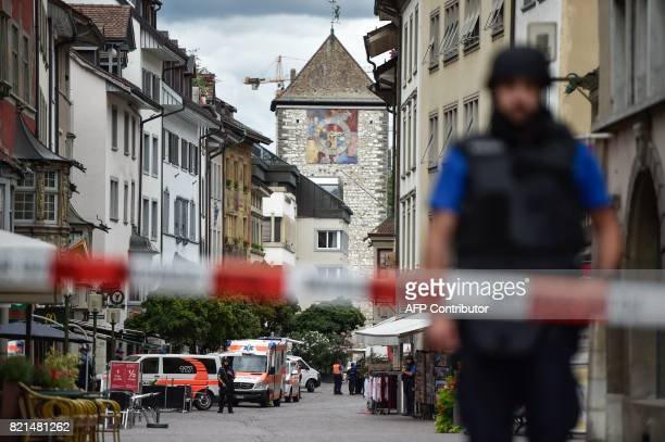 Police and ambulance cars are seen in the old quarter of Schaffhausen northern Switzerland on July 24 after a man armed with a chainsaw injured at...