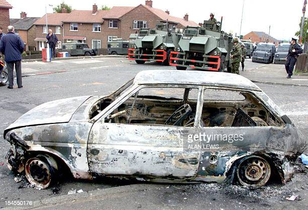 Police and army make their way past a burnt out vehicle on Ardoyne Rd in North Belfast 22 June 2001 this morning as the dispute between catholics and...