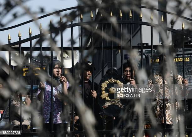 Police and court staff look out from behind the gate of the Indonesian highcourt building in Jakarta on May 12 as protesters gather to demand the...