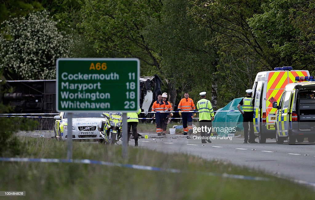 Police and emergency personnel stand by an overturned coach following a road crash on May 24, 2010 in Keswick, England. Three people were killed in the accident involving a school coach, a minibus and a car.