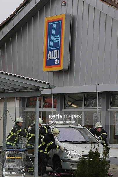 Police and emergency rescue workers stand at the site of an accident in which a construction crane fell onto part of an Aldi supermarket on December...