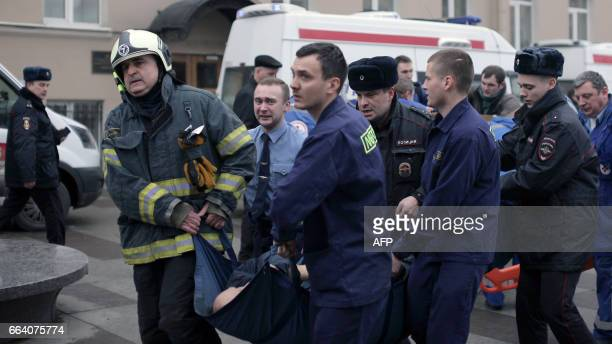 Police and emergency services personnel carry an injured person on a stretcher outside Technological Institute metro station in Saint Petersburg on...