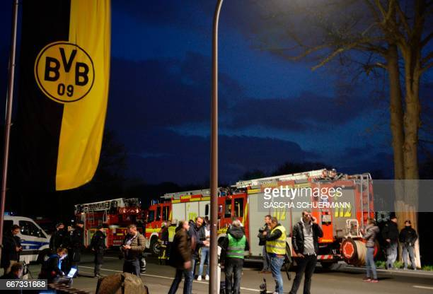 Police and firefighhters are seen near the site wher Borussia Dortmund's bus was damaged by an explosion some 10km away from the stadium prior to the...
