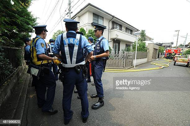 Police and firefighters inspect the site of a plane crash in Chofushi outskirt of Tokyo Japan on July 26 2015 A small plane crashed into a...