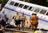 Police and firefighters Rescue inspect Amtrak's 'Capitol Limited' which derailed 29 July 2002 with approximately 190 passengers and 12 crew in...