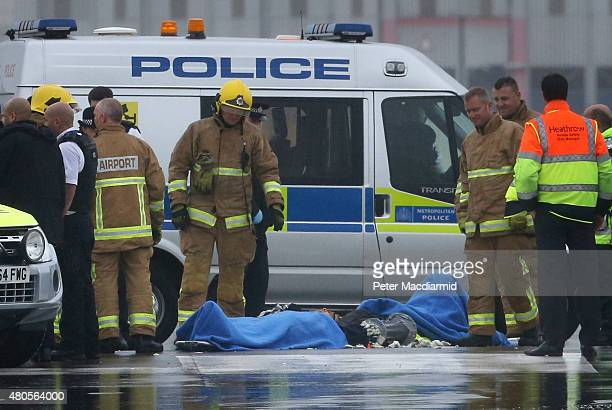 Police and firemen surround the last two remaining protestors occupying part of the northern runway at Heathrow Airport on July 13 2015 in London...