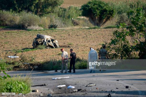 Police and forensic experts inspect the wreckage of a car bomb believed to have killed journalist and blogger Daphne Caruana Galizia close to her...