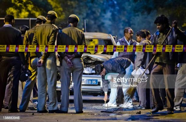 Police and forensic officers examine a damaged Israeli embassy vehicle after an explosion on February 13 2012 in New Delhi India A minor bomb blast...