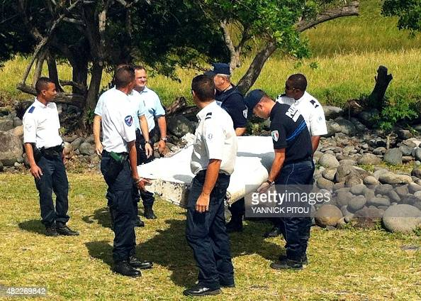 Police and gendarmes carry a piece of debris from an unidentified aircraft found in the coastal area of SaintAndre de la Reunion in the east of the...