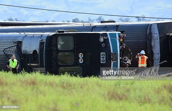 Police and investigators stand beside a turned over carriage following a collision with a truck that was hit by a Los Angelesbound Metrolink train in...