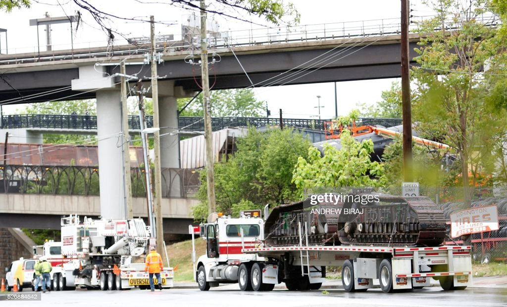 Police and maintenance vehicles are seen at the scene of CSX freight train derailment near the Rhode Island Avenue metro station in Washington, DC, on May 1, 2016. As many as ten cars derailed from a train heading to North Carolina from Cumberland, Maryland. A leak of Sodium hydroxide was said to be leaking from a tanker, but was plugged by emergency responders and hazmat crews. Sodium hydroxide is primarily used in the manufacturing of various household products including paper, soap and detergents. No injuries were reported. / AFP / Andrew Biraj