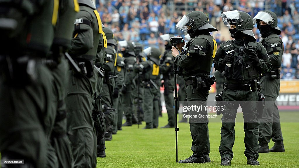 Police and Mannheim supporters face each other on the pitch after the 3. Liga playoff leg 2 match between Waldhof Mannheim and Sportfreunde Lotte at Carl-Benz-Stadion on May 29, 2016 in Lotte, Germany.
