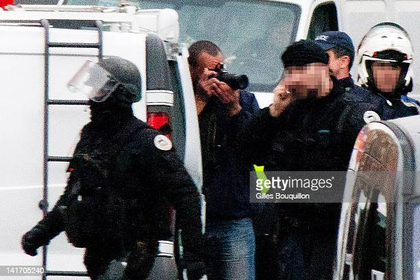 Police and members of the emergency services surround the property during an operation to arrest suspected gunman Mohammed Merah on March 22 2012 in...