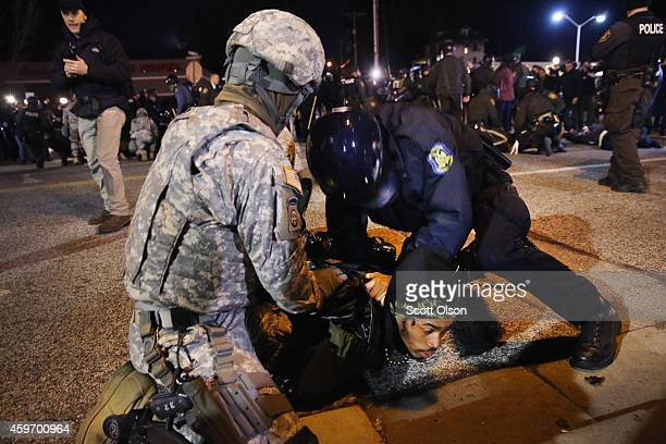 Police and national guard arrest a demonstrator outside the police station November 28 2014 in Ferguson Missouri The Ferguson area has been...