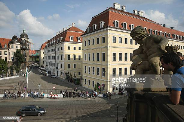 Police and onlookers stand outside the Hotel Taschenbergpalais Kempinski Dresden on the first day of the Bilderberg Group gathering on June 9 2016 in...