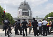 Police and other officials stand outside the US Capitol and the Capitol Visitor Center after the building was evacuated due to reports of a fire in...