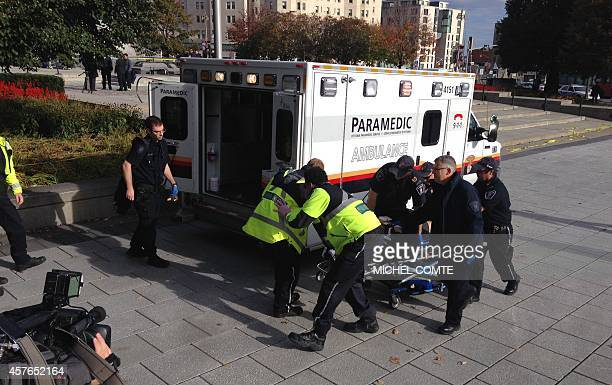Police and paramedics transport a wounded Canadian soldier on October 22 2014 in Ottawa Ontario Canadian police backed by armored vehicles surrounded...